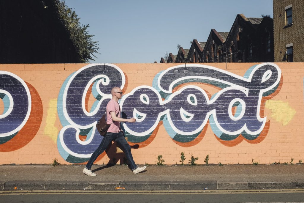 man walking infron of graffiti